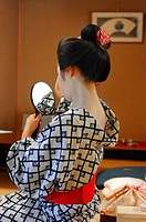 A MAIKO'S APPRENTICE GEISHA TRADITIONAL MAKEUP AND HAIRDO. CHIGNON IN THE FORM OF A PEACH WARESHINOBU AND ADORNED WITH SILK RIBBONS KANOKO, GION DISTR...