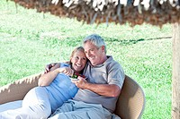 Happy mature couple eating fruit outdoors