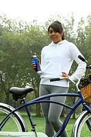 Young female standing next to bicycle