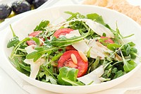 Rocket salad with tomato and pecorino as closeup