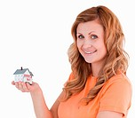 Cute woman holding an house model on a white background