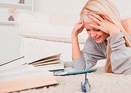 Attractive blond woman lying on a carpet being angry with her computer