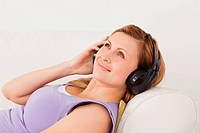 Smiling blond_haired woman listening to music lying on the sofa