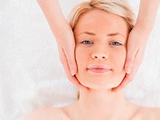 Smiling blond_haired woman getting a massage on her face in a Spa centre