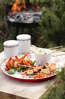 Barbecued prawn skewers on wooden table