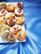 Elegant canapés on white board over blue fabric
