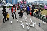 Guilin (China): people feeding pigeons city main square