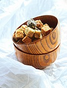Japanese rice cracker squares in wooden bowl