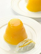 Orange jelly on white plate with dollop of Greek yoghurt
