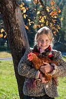 Austria, Salzburg, Flachau, Girl holding hen in farm garden, smiling