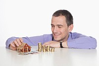 Mature man with coins and toy house