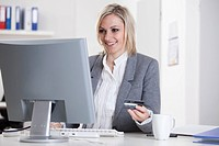 Germany, Bavaria, Munich, Businesswoman with credit card and using laptop