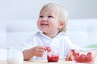 A small child eating squashed strawberries