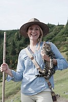 Austria, Salzburg Country, Filzmoos, Young woman with cat, smiling, portrait