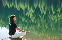Austria, Styria, Mid adult woman meditating at lake duisitzkar in schladming