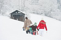 Austria, Salzburg, Hüttau, Family with lantern walking through snow
