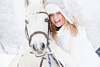 Austria, Salzburg, Hüttau, Young woman with white horse, smiling
