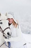 Austria, Salzburg Country, Hüttau, Woman with horse standing in snow