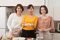 Three mid adult women showing homemade cake