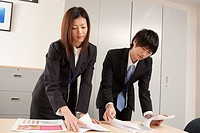 Young businessman and businesswoman preparing documents