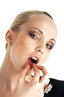 Close-up portrait of young blond model eating a candy over white