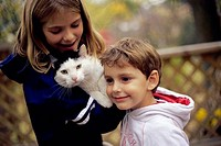 Side profile of a boy and a girl holding a cat