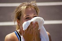 Young woman wiping her face with a towel