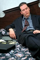 Businessman lying on a bed