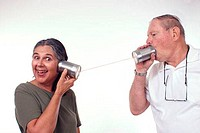 Close_up of a senior man and a senior woman using a tin can phone