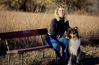 Portrait of a young woman sitting on a park bench with her dog