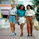 Portrait of three young women walking on the sidewalk