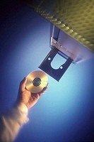 Low angle view of a human hand inserting a CD into a CD_Rom drive