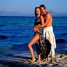 Side profile of a young couple hugging on the beach