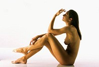 Side profile of a naked young woman sitting on the floor
