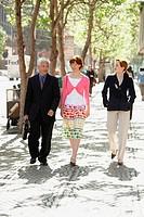 Businessman with two businesswomen walking on a sidewalk