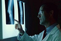 Close_up of a male doctor looking at x_rays on a lightbox