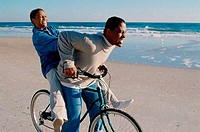 Young couple riding a bicycle on the beach