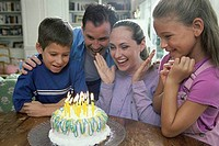 Parents with their son and daughter in front of a birthday cake