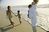Young couple walking on the beach with their son and daughter