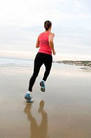 Rear view of a mid adult woman jogging on the beach