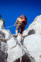 Low angle view of a young woman climbing a mountain