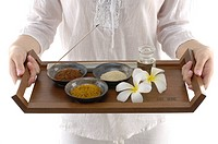 Woman holding spa products in a tray