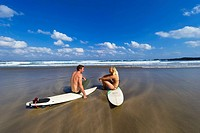 Two people relax on surfboards by the ocean and talk