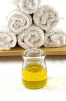 Massage oil bottle near rolled towels
