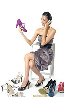 Woman looking at a shoe and talking on a mobile phone (thumbnail)