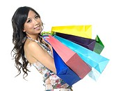 Woman carrying shopping bags and smiling (thumbnail)