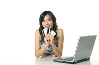 Woman showing credit cards near a laptop