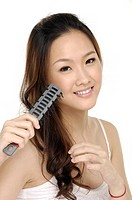 Combing hair. Attractive young lady with comb on white background