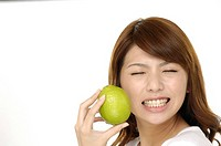 A woman with a lime. The sour flavor of the lime made her make a funny face