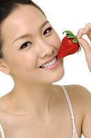 Young asian woman in white dress eating strawberries. Isolated on white background